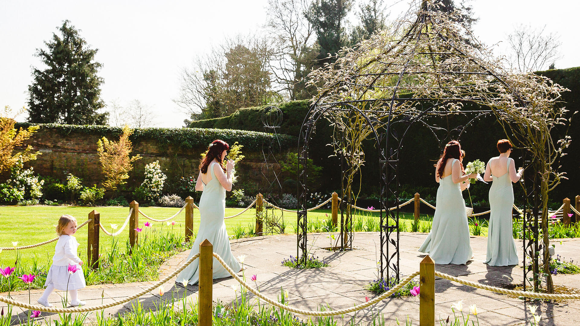A bride and her bridesmaids make their way to the wedding reception through the romantic Walled Garden