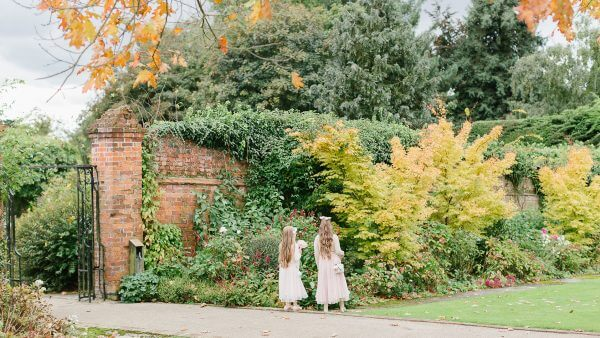 Flowers girls walk down the outdoor wedding aisle during a beautiful autumn wedding day