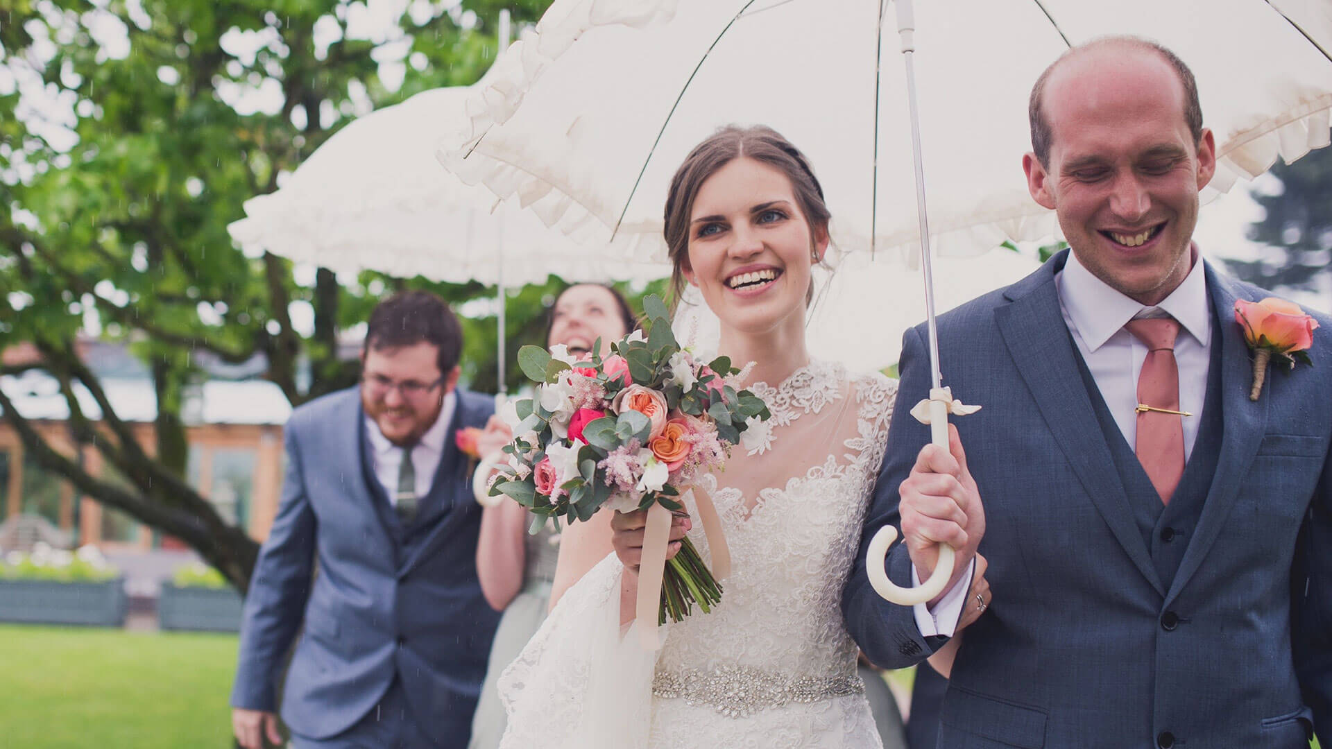 A bride carries a vintage wedding umbrella with gorgeous spring wedding flowers - pink flowers