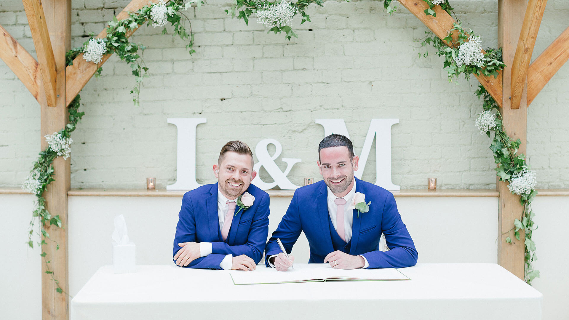 A happy couple sign the register and celebrate their gay marriage and wedding at Gaynes Park