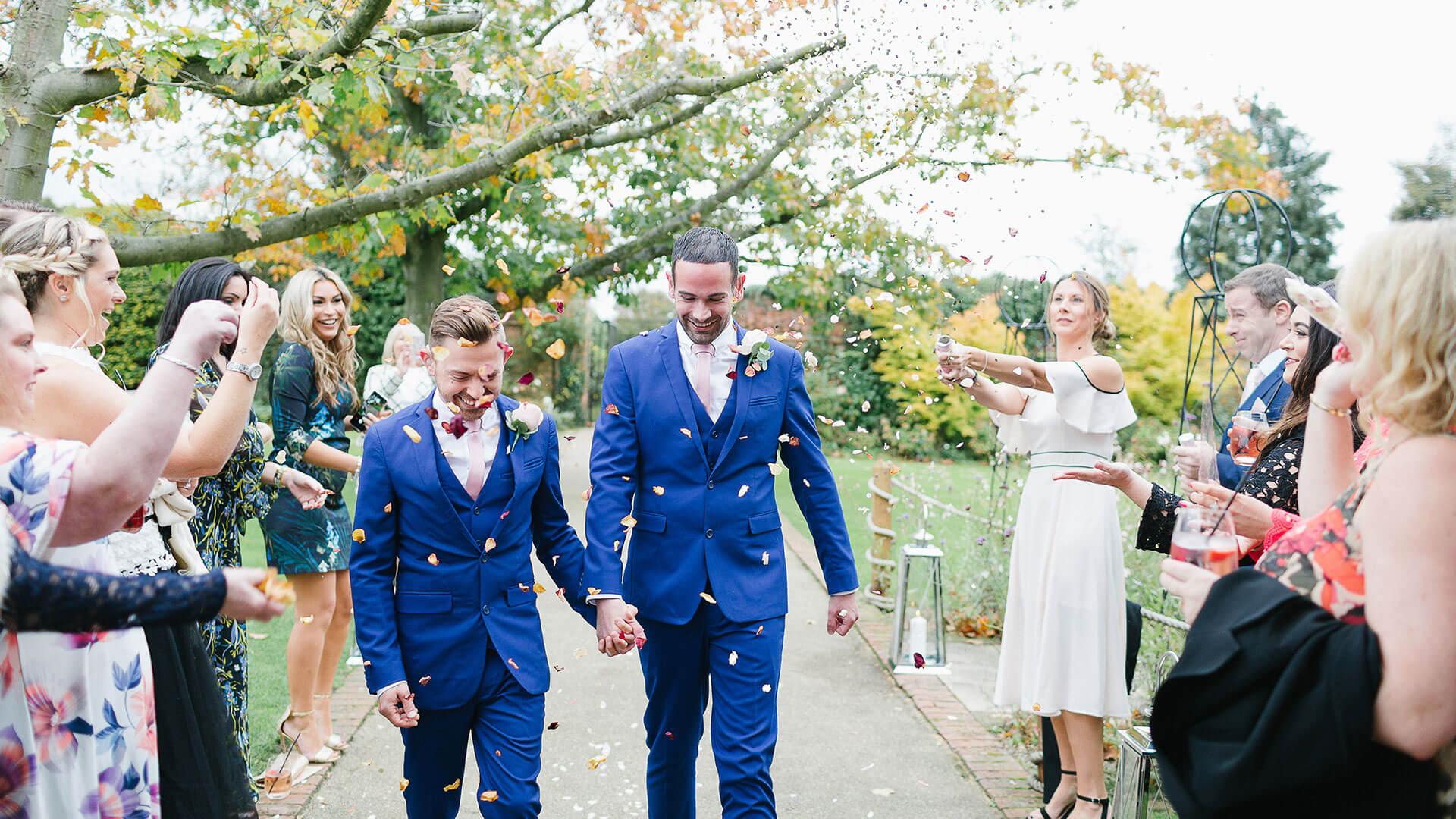 A happy couple are celebrated walking down the long walk - gay wedding