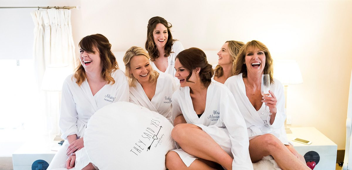 Bride and her bridesmaids laughing while getting ready for the big day