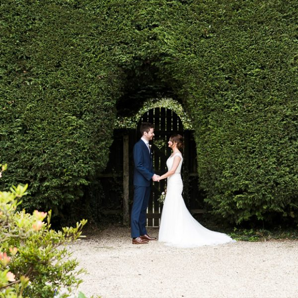 Bride and groom posing for photos in the Walled Garden at Gaynes Park