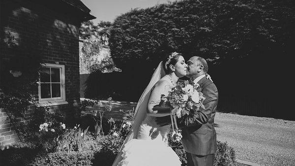 Father kisses bride by the Apple Loft cottage