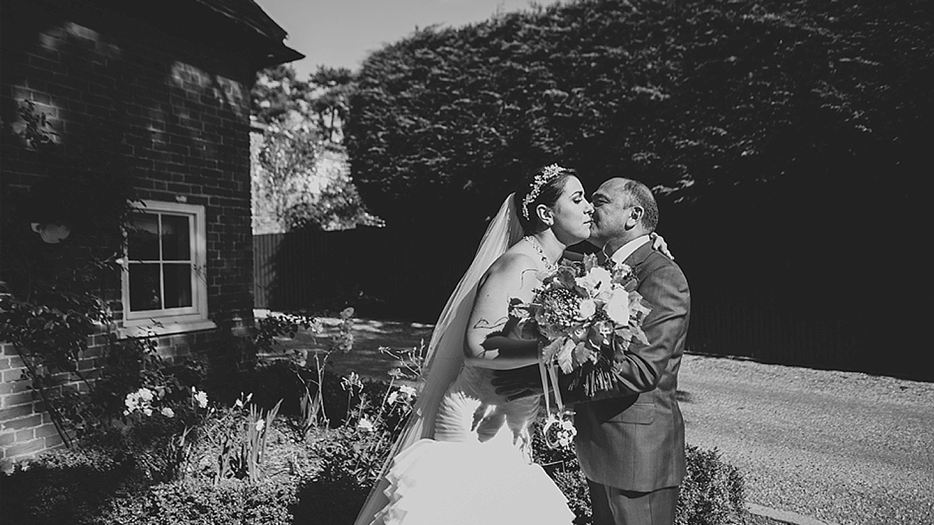 Father kisses bride by the Apple Loft cottage