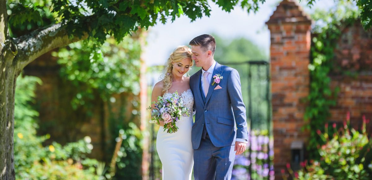 Bride and groom enjoy the Gaynes Park gardens during their summer wedding