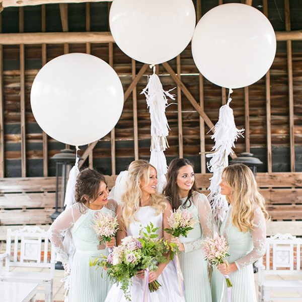 A bride and bridesmaids stand together in the Gather Barn holding three huge white balloons