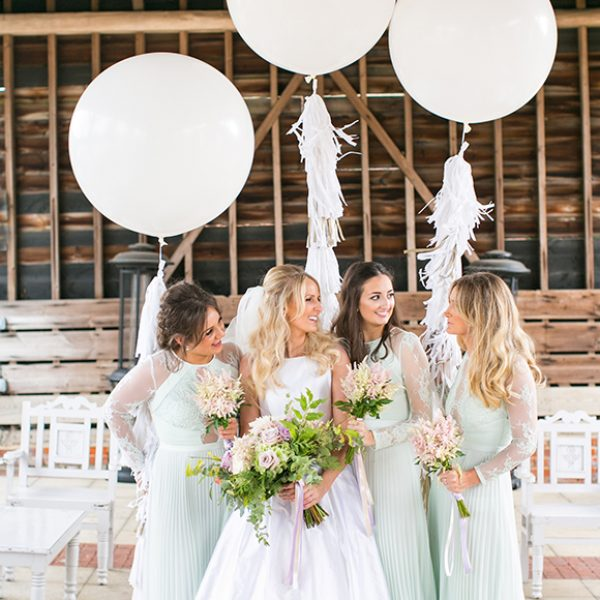 Brides and bridesmaids wearing pastel coloured dresses