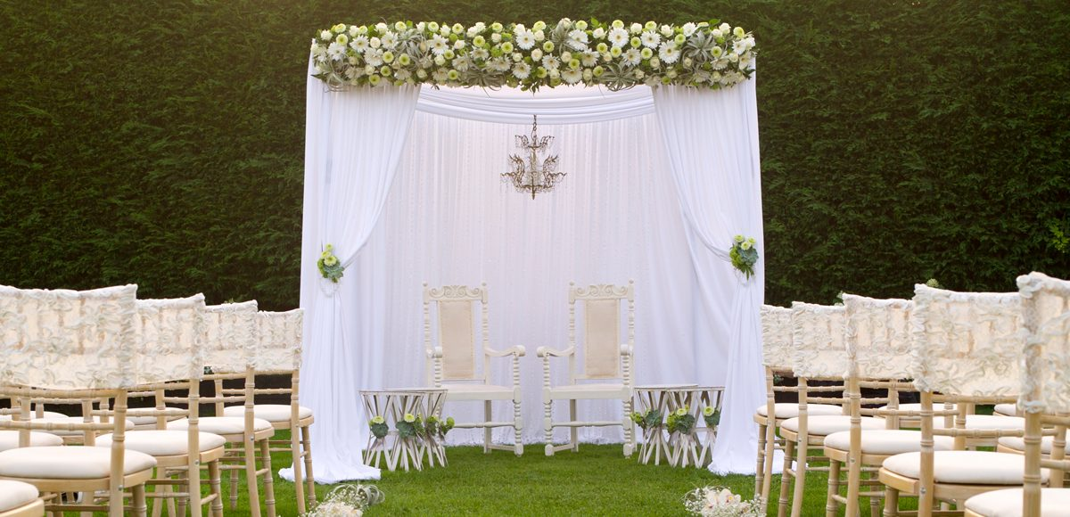 A white canopy for the outside wedding ceremony stands in the beautiful gardens at Gaynes Park