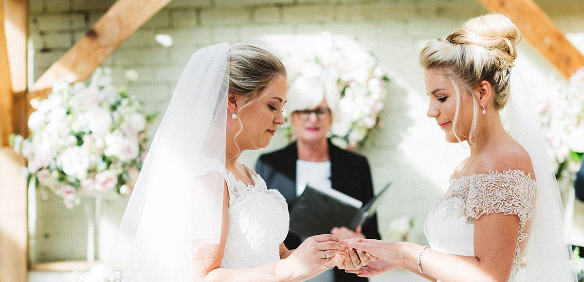 Bride and groom exchanging wedding rings in the Orangery