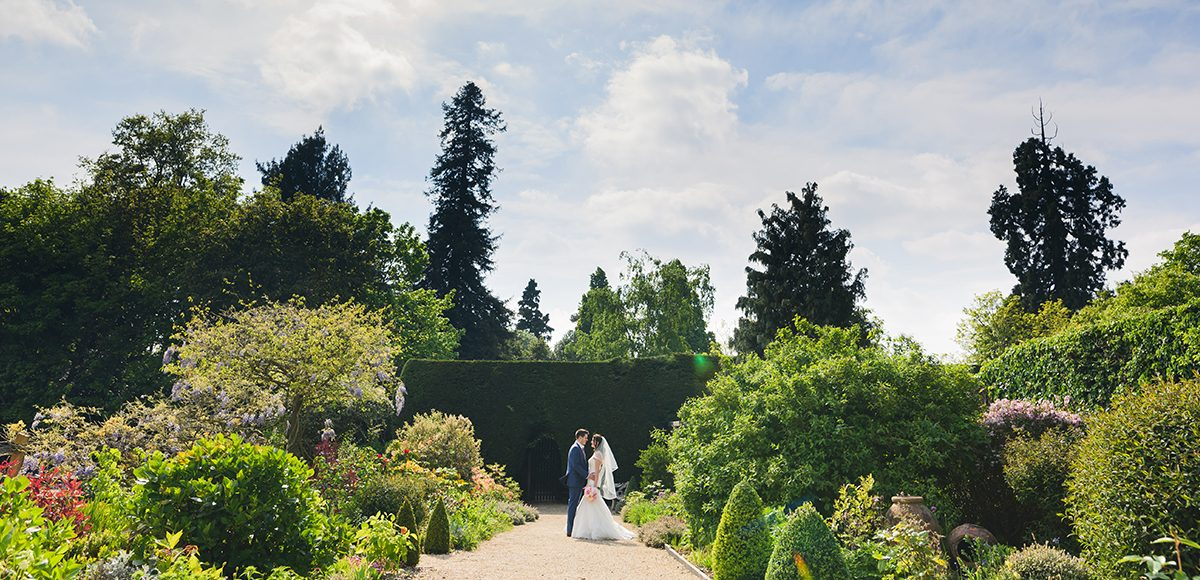 A bride and groom share a moment in the stunning gardens at one of the finest wedding venues in Essex
