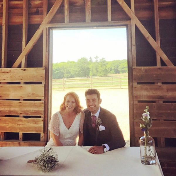 A happy couple sign the register inside the Gather Barn which is perfect for an outside wedding