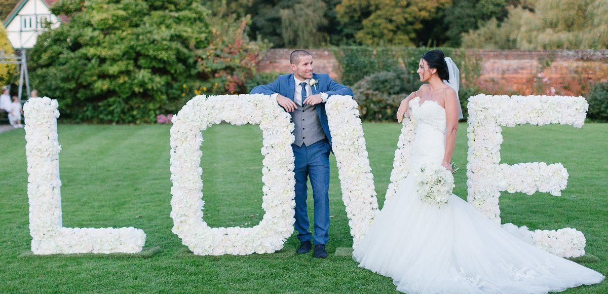 Bride and groom stood next to a love letter sign made out of flowers