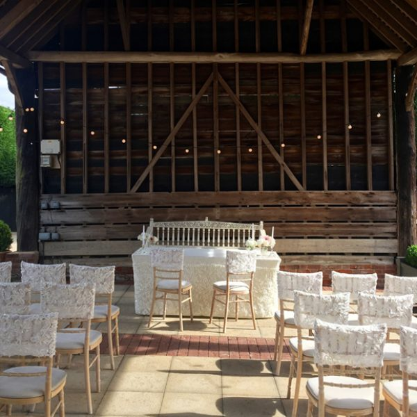 Chairs are dressed in white chair covers for this outside wedding ceremony in the Gather Barn