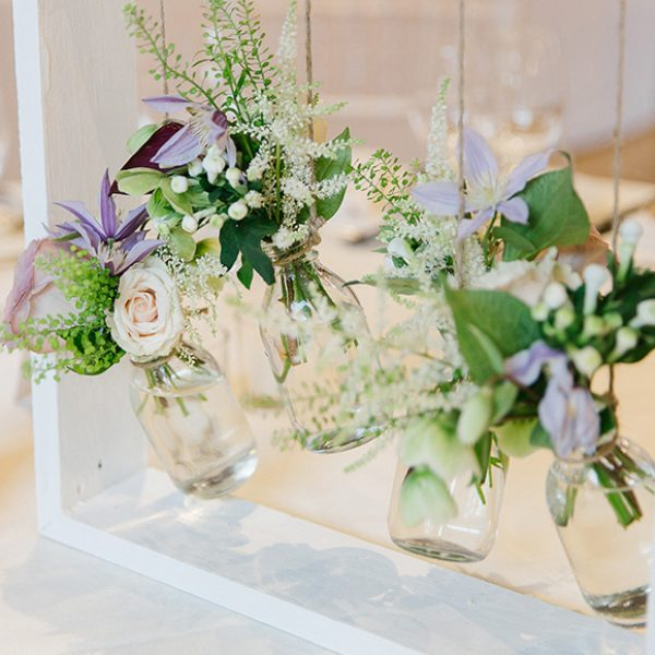 A collection of small glass jars filled with spring flowers hang from a white wooden box – wedding ideas