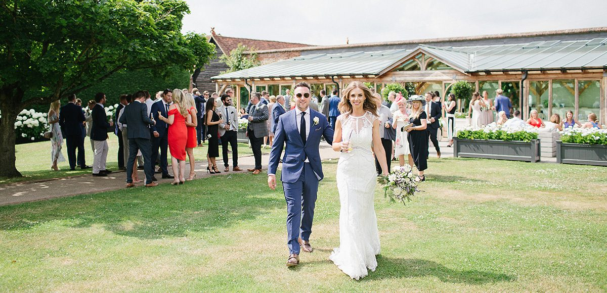 A bride and groom stroll into the Walled Garden to enjoy a drinks wedding reception after the wedding ceremony