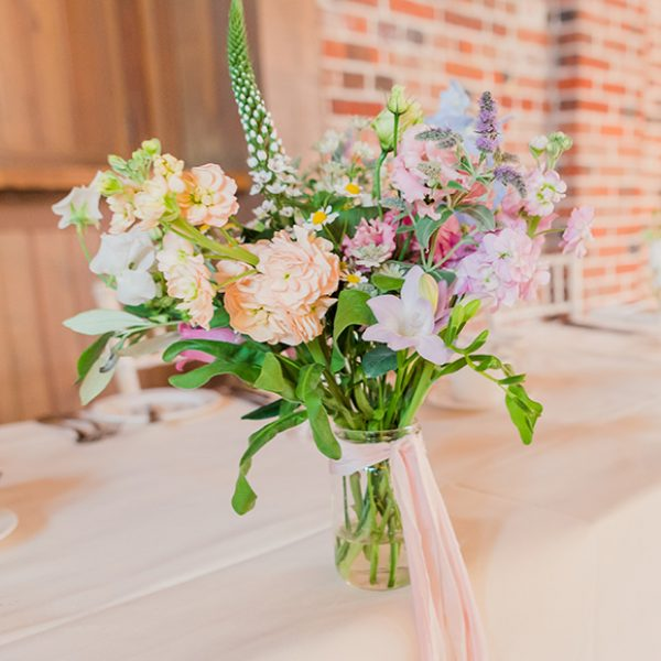 Beautiful pastel coloured flowers in glass jars tied with pink ribbon look beautiful for a spring wedding