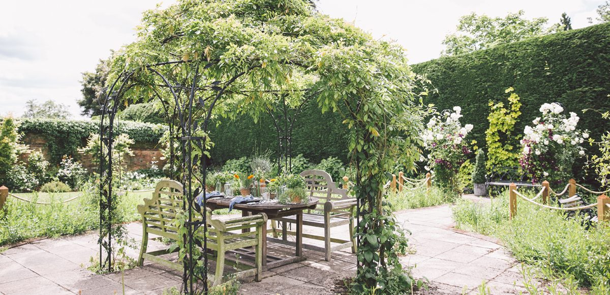 The wrought iron Pavilion is adorned with foliage for a natural feel and is perfect for an outside wedding