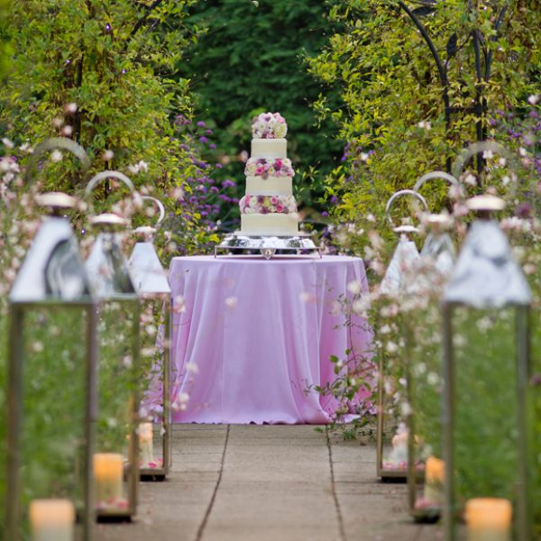 beautiful three-tier wedding cake covered with flowers makes a stunning feature