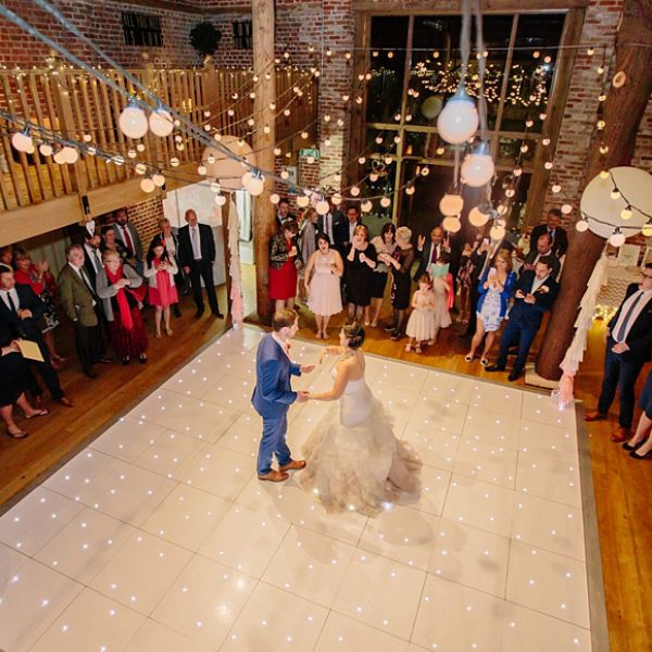 The bride and groom enjoy their first dance in the Mill Barn at Gaynes Park – wedding venues Essex