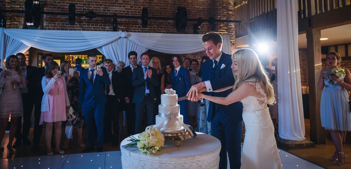 The newlyweds cut the wedding cake amongst their wedding guests in the Mill Barn at Gaynes Park in Essex