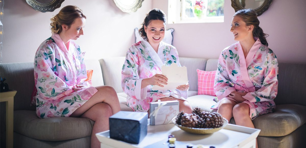 Bridesmaids take a moment to open their wedding gifts in the Apple Loft before a beautiful wedding at Gaynes Park