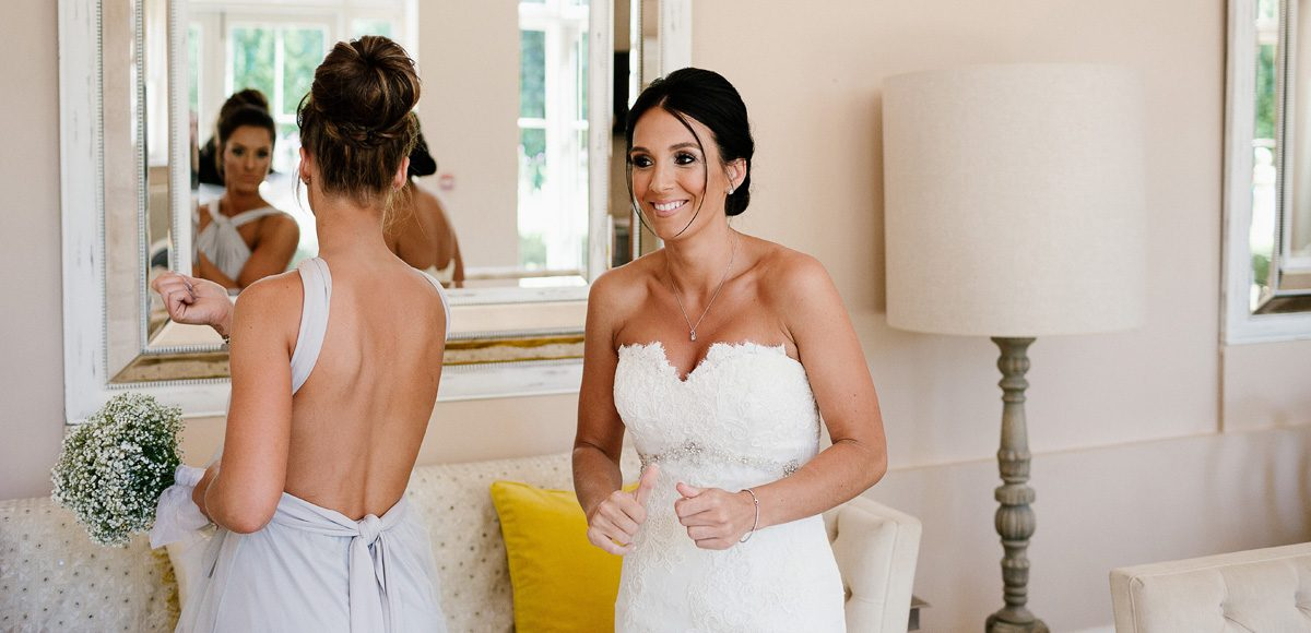 A bride and her bridesmaid take a moment in the Coach House before the wedding ceremony at Gaynes Park in Essex