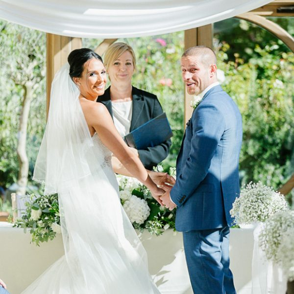 The bride and groom share a moment of laughter at their wedding ceremony in the Orangery at Gaynes Park