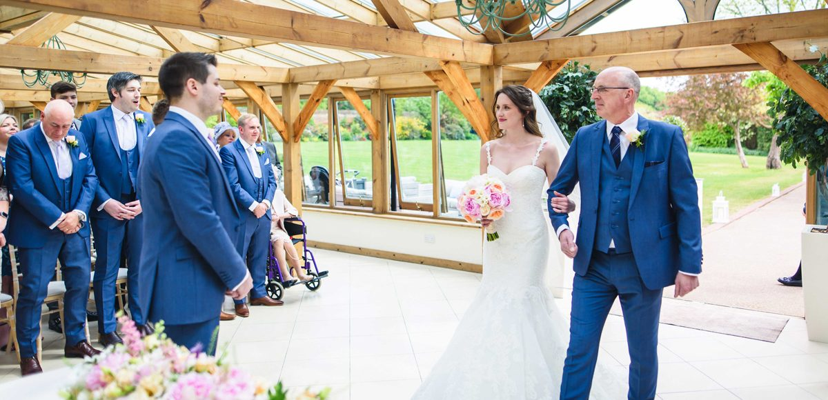Father and daughter walk down the wedding aisle in the Orangery at Gaynes Park in Essex