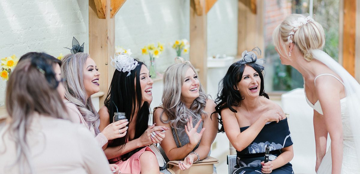 The bride chats to her wedding guests in the stunning Orangery at Gaynes Park in Essex