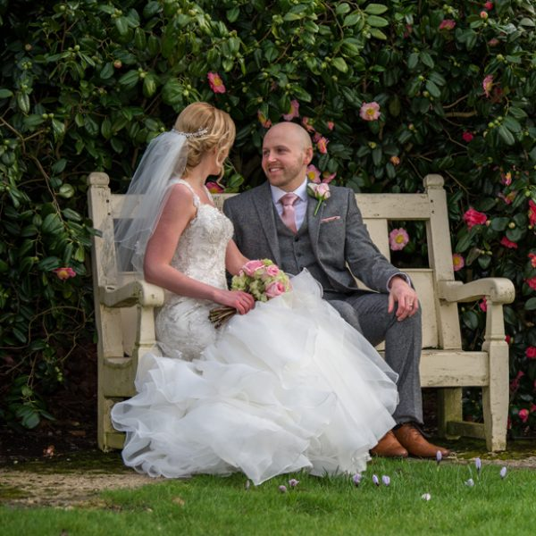 The bride and groom take a moment away from guests to enjoy the gardens at Gaynes Park