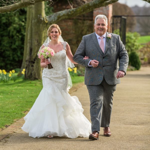 The bride and her father make their way down the Long Walk at Gaynes Park wedding venue in Essex