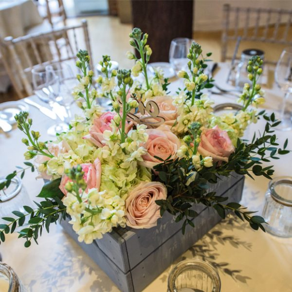 Pink roses and cream flowers were used in The Mill Barn at Gaynes Park for stunning spring centrepieces