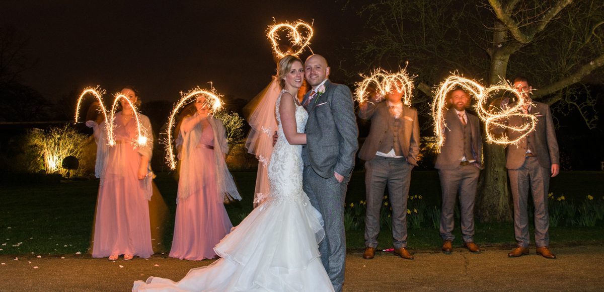 The wedding party create Mr and Mrs in a sparkler send off for the new husband and wife