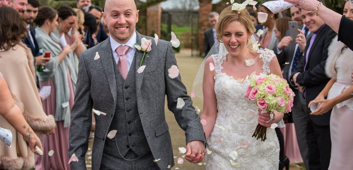 The newlyweds enjoy a confetti moment on The Long Walk at Gaynes Park in Essex