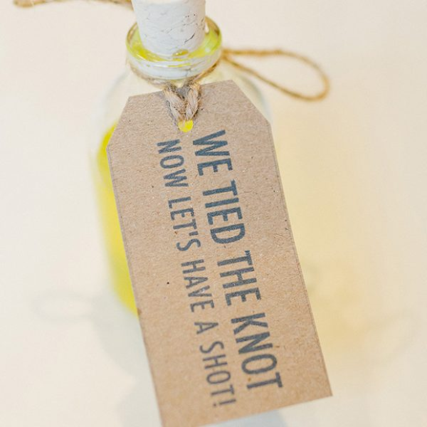 Bottles of limoncello decorated with gift tags were used as wedding favours – wedding ideas