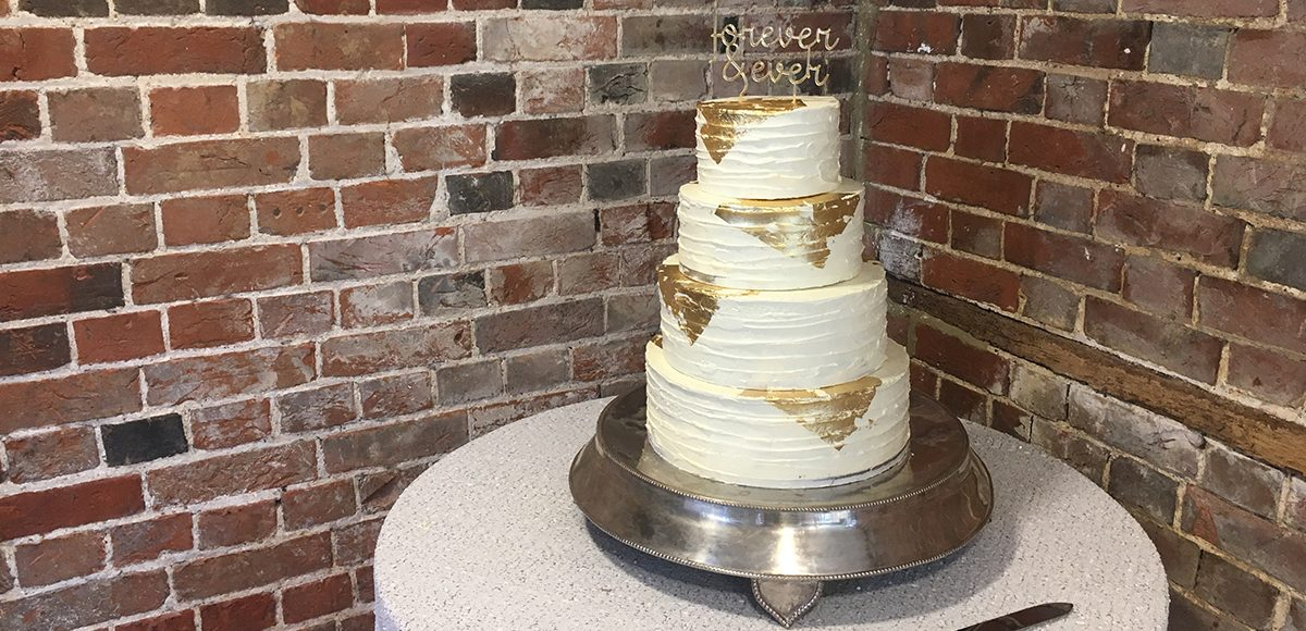 A stunning four-tiered wedding cake is decorated in buttercream and gold leaf for an indulgent look