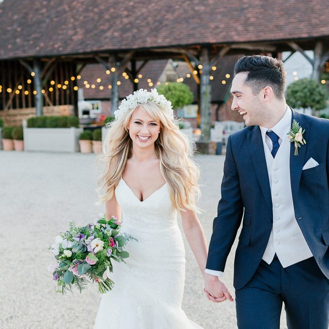 The bride and groom take a stroll around the grounds at the exclusive use wedding venue in Essex