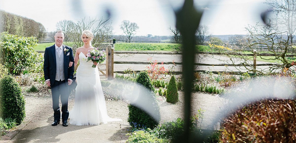 The father of the bride prepares to walk his daughter down the aisle at Gaynes Park in Essex