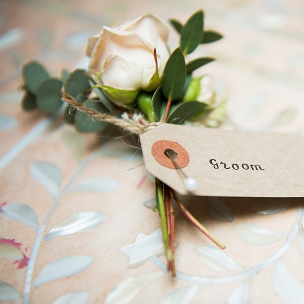 A tag attached to a white rose button hole for the groom adds a great vintage wedding look