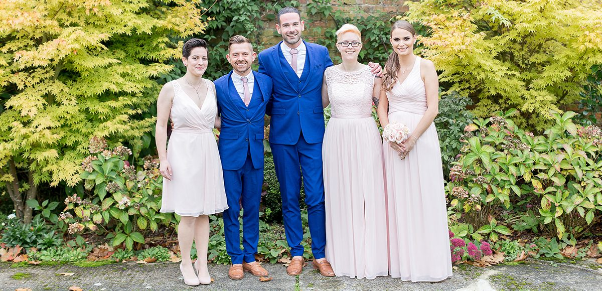 For the wedding day at Gaynes Park the grooms wear navy suits with their best women in blush pink bridesmaid dresses