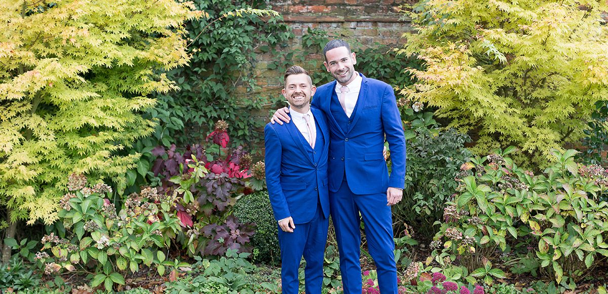 The grooms look happy in navy wedding suits in the gardens at the Essex wedding venue