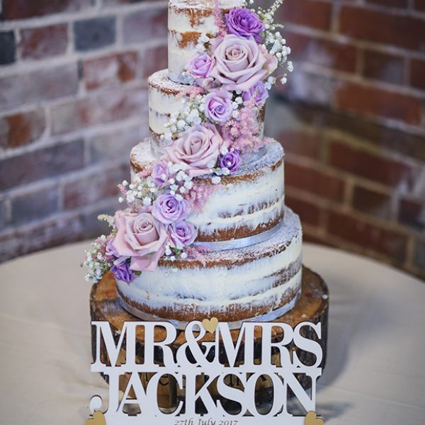 A four-tiered semi-naked wedding cake is decorated with pink and purple roses