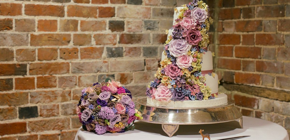 This four-tiered traditional white wedding cake is draped in stunning multicoloured icing flowers that match the bridal bouquet