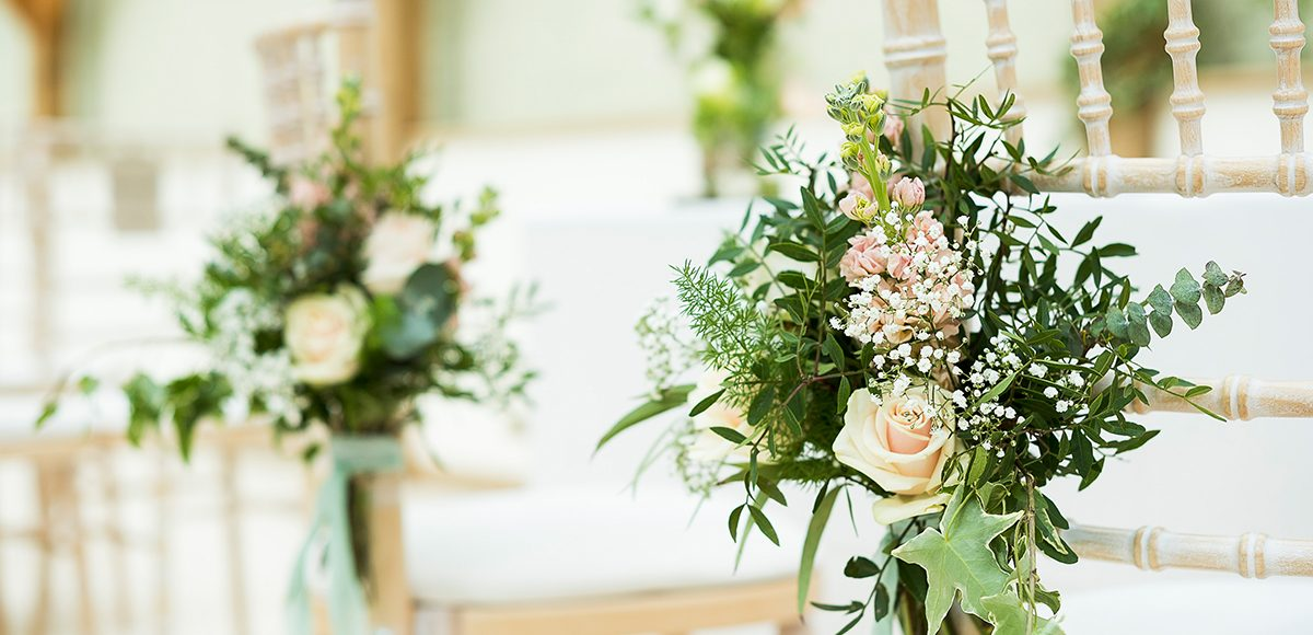 Wedding flowers are attached to aisle end chairs in the Orangery at Gaynes Park in Essex