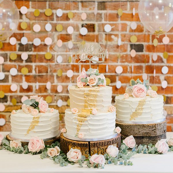 The couple chose three wedding cakes that were displayed on logs and topped with pink icing flowers for their wedding at Gaynes Park