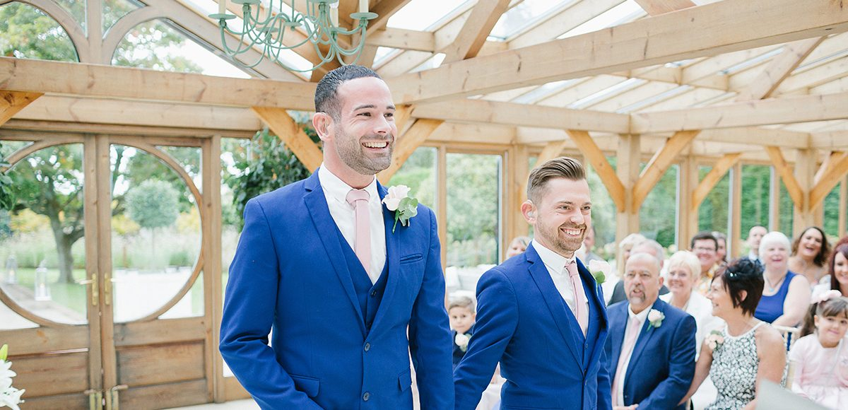The grooms enjoy their wedding ceremony in the Orangery at Gaynes Park wedding venue in Essex
