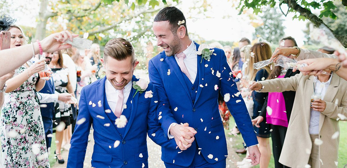 The wedding guests shower the grooms in wedding confetti after the wedding ceremony at Gaynes Park in Essex