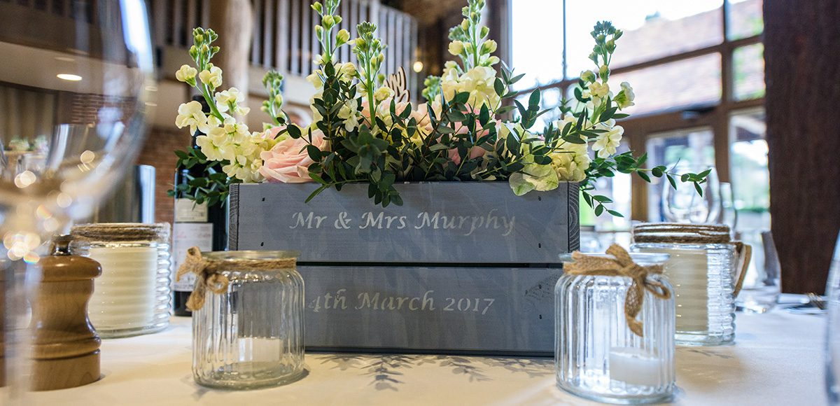 Wedding flowers are surrounded by glass jars for a stunning vintage wedding table centerpiece