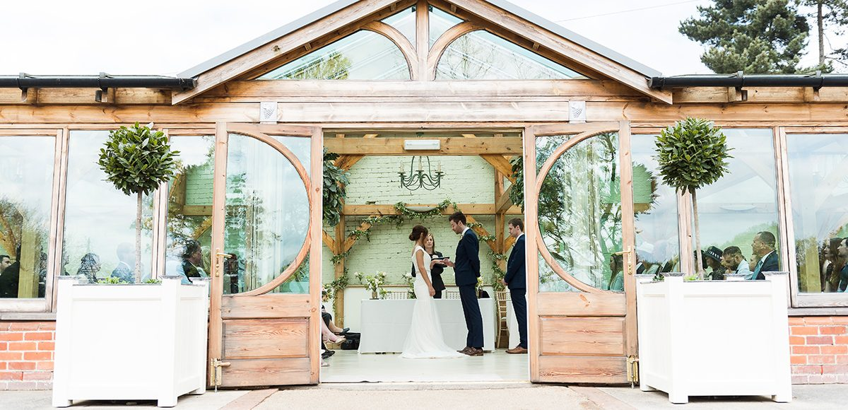 Looking in to the Orangery at Gaynes Park in Essex as the bride and groom say I do